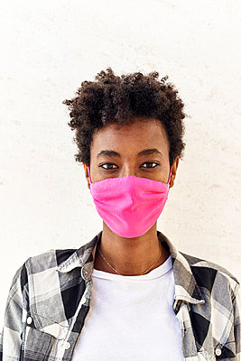Afro woman wearing pink mask against white wall - p300m2241781 by Veam