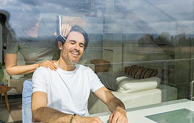 Woman cutting man's hair using electric razor while sitting at home seen through glass - p300m2277244 by Jose Carlos Ichiro