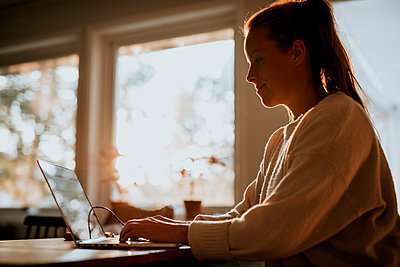 Woman using laptop at home - p312m2237142 by Anna Johnsson