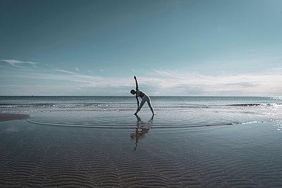 Woman practising yoga on beach - p429m2019414 by Ingolf Hatz