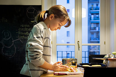 Girl standing in a kitchen, preparing food. - p429m2200775 by OPIFICIO 42