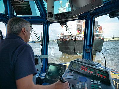 Captain steering tugboat in wheelhouse - p429m726962f by Monty Rakusen
