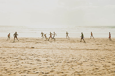 Football players on a beach - p445m1552774 by Marie Docher