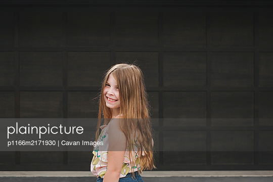 Portrait of a pretty young girl smiling at the camera - p1166m2171930 by Cavan Images