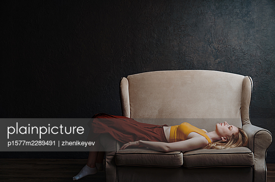 Beautiful pensive women at home laying on a sofa - p1577m2289491 by zhenikeyev