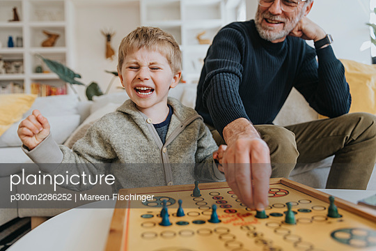 Son winning against his father while playing a board game at home, Viersen, NRW, Germany - p300m2286252 von Mareen Fischinger