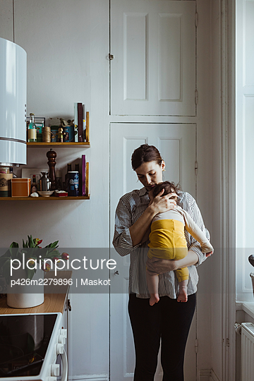 Mother carrying baby boy while standing in kitchen - p426m2279896 by Maskot