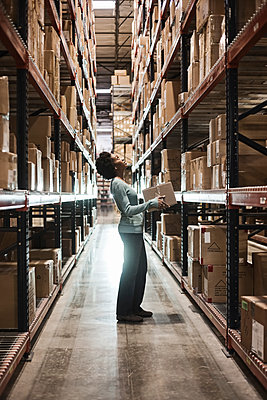African American female warehouse worker checking inventory and carrying a box in an aisle of products stored in cardboard boxes, on large racks in a large warehouse distribution centre. - p1100m1575481 by Mint Images