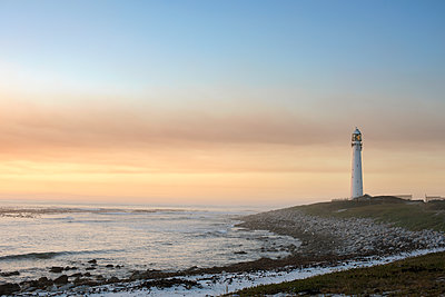 Lighthouse by sea against sky during sunset - p1166m1226183 by Cavan Images