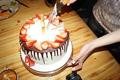 A woman cuts a birthday cake and puts it in saucers - p1166m2280323 by Cavan Images