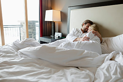 Affectionate couple in bathrobes cuddling on luxury hotel bed, enjoying romantic weekend - p1192m2047353 by Hero Images