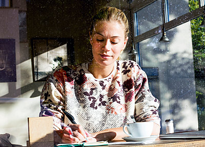Portrait of woman in a cafe writing on notebook - p300m2070309 by Linda Meyer