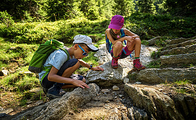 Boy and girl on a hiking trip watching ants, Passeier Valley, South Tyrol, Italy - p300m2154715 by Dirk Kittelberger