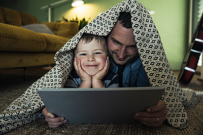 Smiling father and son with digital tablet lying under blanket in living room - p300m2286952 by Uwe Umstätter