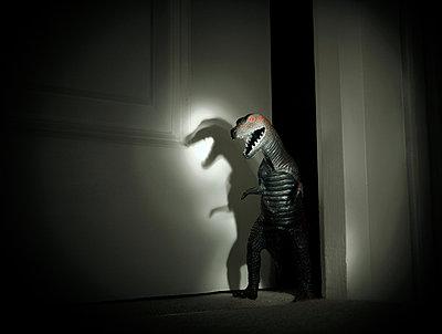 Toy dinosaur spotlit in darkened doorway - p429m1494668 by Seb Oliver