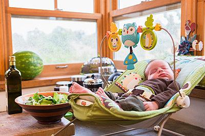 Caucasian newborn sleeping in baby seat - p555m1463837 by Marc Romanelli