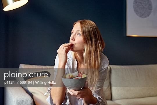 Junge Frau nascht Obst - p1124m1589194 von Willing-Holtz