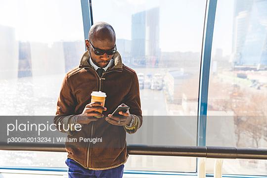 Businessman with coffee to go looking at smartphone - p300m2013234 von William Perugini