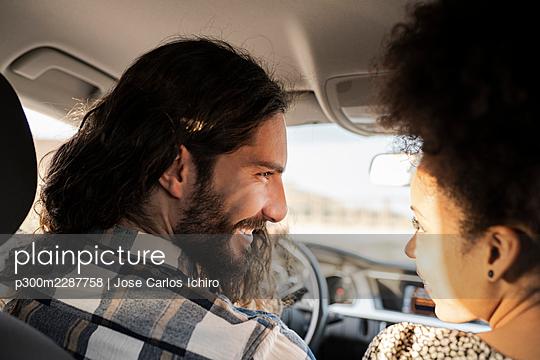 Girlfriend looking at smiling boyfriend in car - p300m2287758 by Jose Carlos Ichiro