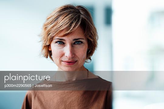 Businesswoman staring in office - p300m2290565 by Joseffson