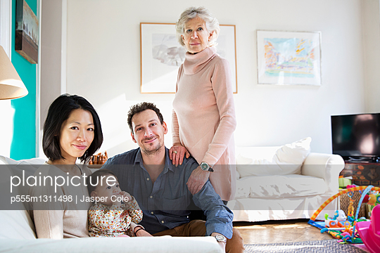 Family and grandmother smiling in living room - p555m1311498 by Jasper Cole