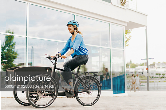 Young woman rides a cargo e-bike - p608m2192838 by Jens Nieth