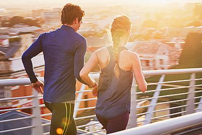 Runner couple running on sunny urban footbridge at sunrise - p1023m1201836 by Ryan Lees