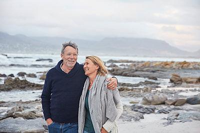 Smiling senior couple walking on winter beach - p1023m1217909 by Ryan Lees