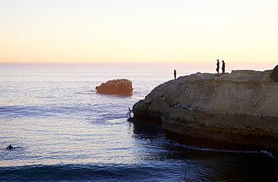 Surfers of rocky coast - p1106m1589466 by Angela DeCenzo