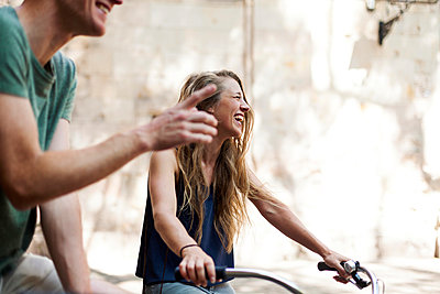 Laughing woman with bicycles beside her partner - p300m1156493 by Valentina Barreto