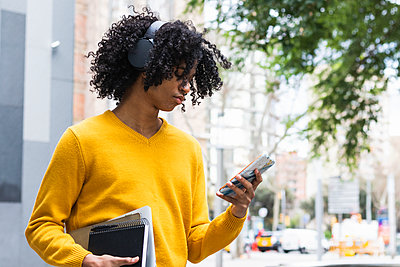 Boy wearing headphones using mobile phone while standing with books outdoors - p300m2267885 by NOVELLIMAGE