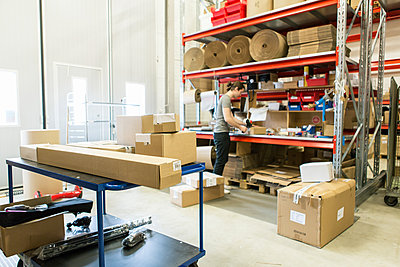 Manual worker packing box in distribution warehouse - p426m1580307 by Kentaroo Tryman