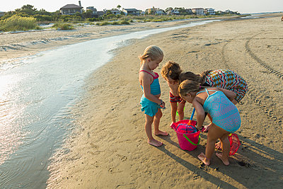 Caucasian boy and girls playing with pail on beach - p555m1522786 by Marc Romanelli