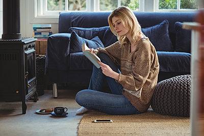 Beautiful woman reading book while having tea in living room - p1315m1229928 by Wavebreak