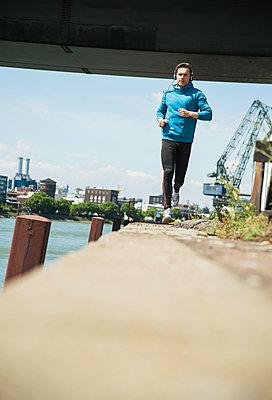 Man with headphones jogging at riverside - p300m1188498 by Uwe Umstätter