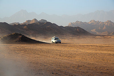 Off-road vehicle on dust in desert against sky during sunset - p300m2132367 by Nadine Ginzel