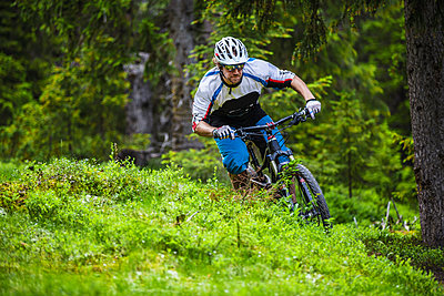 Mountain biker charging down the trail in Valadalen, Sweden. - p343m1090333 by Elias Kunosson