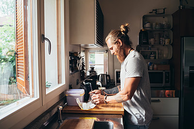 Bearded tattooed man with long brunette hair standing in a kitchen, preparing food. - p429m2202108 by Eugenio Marongiu