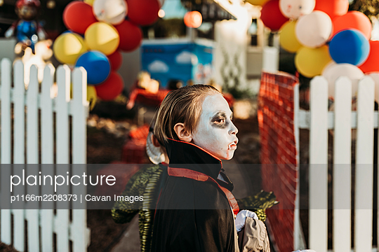 School aged boy dressed as Dracula Trick-or-Treating during Halloween - p1166m2208373 by Cavan Images