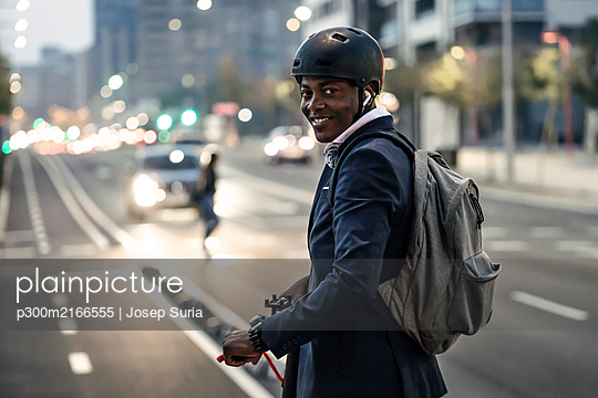 Portrait of smiling businessman with push scooter on bicycle lane in the evening - p300m2166555 by Josep Suria