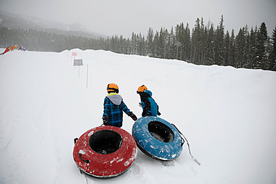 Brothers pulling inner tubes in snow at tube park - p1192m1546612 by Hero Images