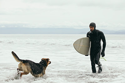 Male surfer with dog carrying surfboard in ocean surf - p1192m1583593 by Hero Images