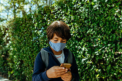 Schoolboy wearing mask using mobile phone while standing by plants - p300m2214182 by Valentina Barreto