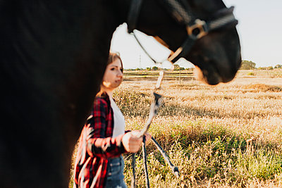 Young woman walking with horse in agricultural field on sunny day - p300m2256978 by Manu Reyes