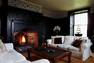 White sofas in black panelled Georgian farmhouse living room - p349m789831 by Brent Darby