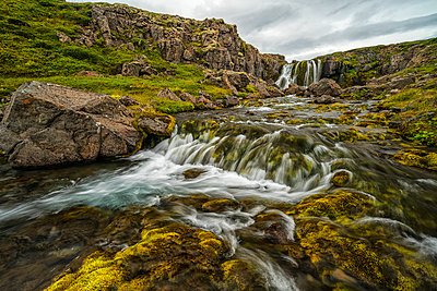 Water falling from rocky cliff to a stream below; Iceland - p442m2074064 by Robert Postma