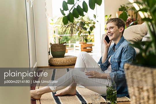 Cheerful woman talking over smart phone while sitting on carpet at home - p300m2214180 by Uwe Umstätter