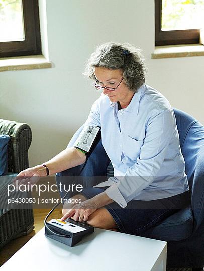 Frau misst Blutdruck  - p6430053 von senior images