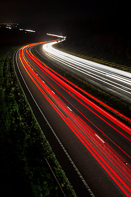 Streaks of coloured light making long lines left by vehicles driving along a road in the night. - p1057m1510624 by Stephen Shepherd