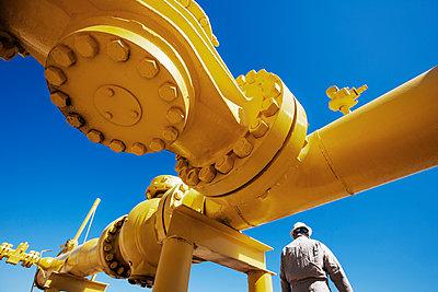 Male worker standing below yellow painted pipeline at oil refinery - p1166m1163857 by Cavan Images